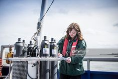 Stock Photo : Female scientist making notes with sea water sampling experiment on research ship