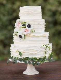 white ruffled wedding cake with flowers and leaves at the base