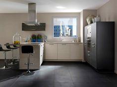 Sol gris foncé, meubles bois clair et gris. Murs blancs
