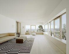 La casa progettata da Architektur 109 a Stoccarda è ruvida e nera all'esterno, ma morbida e bianca all'interno con grandi aperture verso il panorama della città.