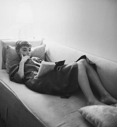 Audrey Hepburn reading on her couch
