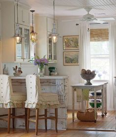How many ways do I love thee, pretty country kitchen? 1. Ruffled slipcovers for stools 2. Chippy corbels and wood for bar 3. Organic window treatment 4. Sweet little table as island with casters for easy movement 5. Glass cabinet doors 6. Wood floors 7. Perfect little pendant lights 8. Beadboard ceiling.... *sigh