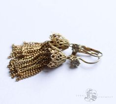 These delicate, glamorous antique tassel earrings feel very contemporary. Gold plated and marked Germany these earrings date before WWII and are most likely from the 1930s. The practical lever back ear wires adorned with paste Rhinestones that still have loads of brilliant flash. These would make lovely, bohemian accents for a modern bride or bridesmaid, but also add some refinement to an every day vintage look. They measure just shy of 2 long.