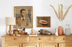 wood cabinet with vintage paintings. / sfgirlbybay
