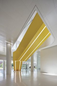Yellow stairways, such as this one leading from the ground-floor entrance to the main lobby, incorporate light fixtures on their undersides. Stair Handrail, Staircase Railings, Staircase Design, Stairways, Commercial Stairs, Commercial Design, Commercial Interiors, Staircase Architecture, Education Architecture