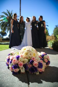 Navy blue flowers; seasonal flowers; Bridal bouquet: Blush garden roses, white ranculus, and Sahara rose; Bridesmaids bouquets: Blush pink roses, white calla   and touch of dark blue anemone