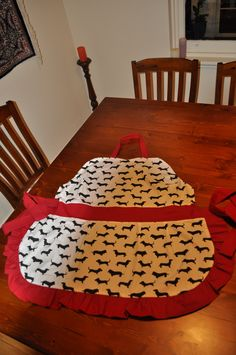 An apron I made for my friend who loves sausage dogs / dachshunds. It has black and white spots on the back so it is reversible.