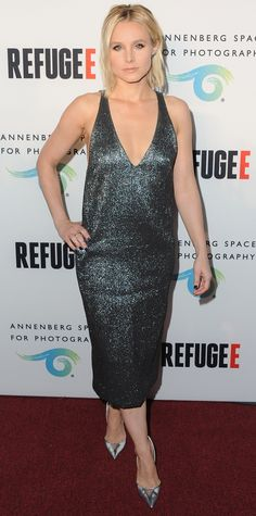 "Kristen Bell played with metallic for the opening of the ""Refugee"" exhibit, lighting up the red carpet in a shimmery gunmetal Camilla and Marc number that she styled with mirrored silver pumps."