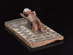Bakongo Science Museum Group Collection © The Board of Trustees of the Science Museum. Carved wooden figure of female reclining on rectangular board, in position ready for a clitoridectomy (?), painted, Bakongo tibe, Congolese, 1880-1930