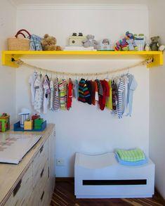 """"""" Singela, a ideia da arquiteta Letícia Arcangeli surgiu como alternativa de menor custo para acomodar roupas no quarto de bebê. A prateleira ganhou um cabideiro de corda preso em ganchos com um nó."""""""