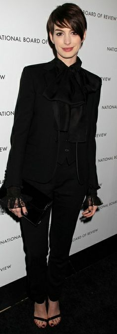 Who made Anne Hathaway's black sandals, black clutch handbag, lace top, and black pants suit that she wore in New York on December 8, 2013? Jacket, pants, and shirt – Yves Saint Laurent  Shoes – Givenchy  Purse- Jill Milan