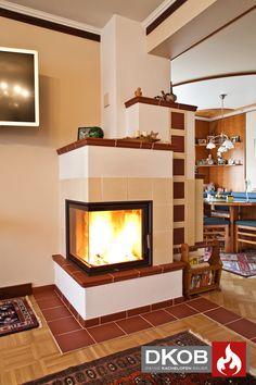 Ein klassischer Kachelofen im schönen Landhausstil. Das großzügige Eckfenster sowie die feine Keramik sorgen nicht nur für Wärme, sondern fördern auch das Raumklima.  Designed by DKOB - Deine Kachelofenbauer