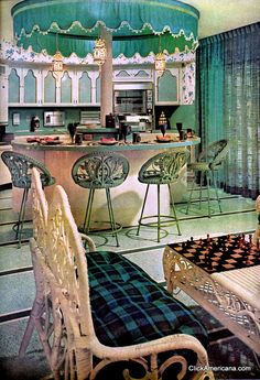 Festive carousel kitchen in turquoise (1966). Wall-to-wall sliding doors. View from the breakfast bar into the living room. All furniture looks like it was lifted from the garden center!