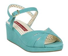 Channel your inner Bettie Page with the tropical Kiki Wedge from B.A.I.T.! This pin-up perfect sandal is crafted from 100% vegan leather in a fresh and breezy aqua tone. A retro-inspired cross band vamp cuts away into cute peep toe so you can show off your pedicure while you're lounging poolside. Slender ankle straps fasten with delicate gold buckles, and a low wedge gives these vintage-inspired shoes the perfect amount of lift. Pair the Kiki Wedge with one of our adorable mini dresses for a…