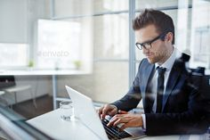 Businessman typing by Pressmaster. Successful young businessman typing on laptop at workplace