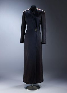 Evening coat (front view) | Elsa Schiaparelli & Jean Cocteau (designers), Lesage (maker) | Made in London, 1937 | Materials: silk jersey, with gold thread and silk embroidery and applied decoration in silk | The design reveals Cocteau's preoccupation with the double image, a motif he consistently returned to in his work. The double image held particular fascination for other artists associated with the Surrealist movement, including Dalí | VA Museum, London