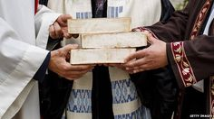 The hands of Rabbi Tovia Ben-Chorin, Father Gregor Hohberg and Imam Kadir Sanci are see as they hold symbolic bricks
