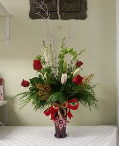 This table arrangement includes fresh cedar and roses! Perfect for the holiday season. Created by Anna's Flowers Inc.