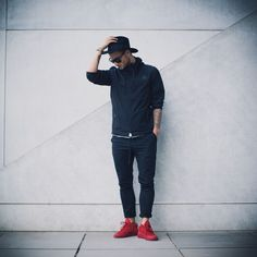 Streetstyle : Black Windbreaker, Red Son of Blades Premium Sneaker, combined with a hat, sunglasses and a black chino