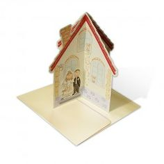 A wedding invitation from the newest collection made from ecru-coloured matte paper. A  3D invitation in the shape of a house. All the elements of the invitation are printed. A bride and groom is attached as an additional application. Text is printed on one of the walls of the house.  The invitation is made with great care and attention to detail.