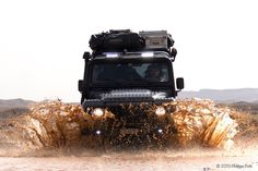Land Rover Defender playing in the muddy river
