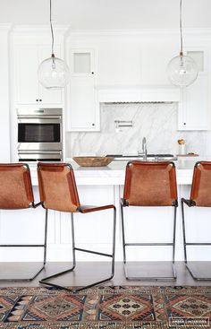 Mid century bar stools on a vintage kilim rug in an open plan all-white kitchen. Perfection!