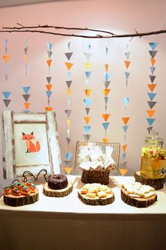 Decorations | Love the simple triangle garland backdrop, the wood slice platters and the framed artwork!