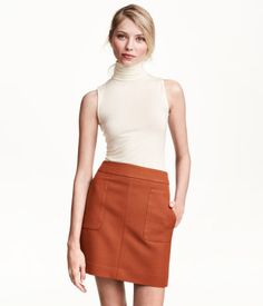 Short skirt in woven fabric with a visible back zip. Unlined.