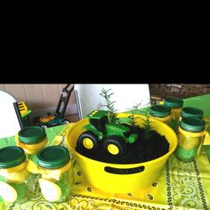 Centerpieces for boy's John Deere birthday party. The jars have homemade green and yellow playdoh that the kids were able to take home as party favors...