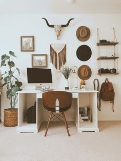 a southwestern boho home office with a macrame hanging, hats, artworks and an animal skull plus a minimal desk and a wooden chair - Shelterness