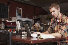 A young man works on his computer at a coffee shop