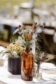 DRESDEN + IAN // burnsville, mn wedding. florals by the bee's knees floral. photos by elizabeth shey. #thebeeskneeswashere  this gorgeous outdoor wedding included lots of bright, colorful wildflower florals, lush silver dollar eucalyptus, and vintage accents. mismatched centerpiece arrangements and bud vases made in a variety of vintage bottles, tins, and vessels was the perfect way to trim the tables.