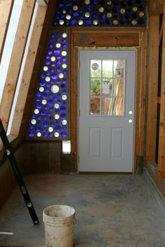 Doors in hallway (bottles- brown, white and green highlights). Wine Bottle Wall, Bottle House, Bottle Art, Natural Building, Green Building, Building A House, Cordwood Homes, Earth Bag Homes, Recycled House