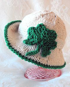 Knitting Pattern for Shamrock Baby Hat - Hat with brim and knit shamrock in 7 sizes from baby to adult, though designer says baby sizes work best. Sizes Newborn, 0-3 mos., 3-6 mos., 6-9 mos., 9-12 mos., toddler/child, adult. Finished product also available. Designed by CottonPickings