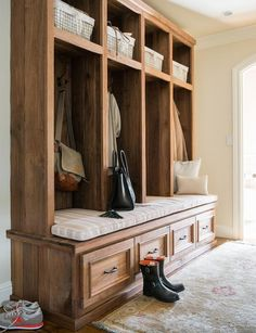 Well designed mudroom features a gold wool rug placed beautifully in front of rustic wood open lockers fitted with shelves holding vintage metal bins and a storage bench accented with bronze pulls and a pink striped bench cushion positioned under iron hooks.