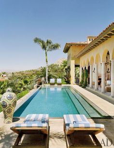 Bookending the pool of a cliffside Mexican villa are Henry Hall Designs chaise longues with striped cushions in a Perennials fabric.
