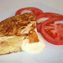 Tortilla de patatas rellena de mozzarella de búfala y ensalada de tomate