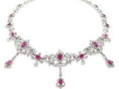 A ruby and diamond festoon necklace, circa 1900. The three central cartouches set with pear-shaped rubies, cushion-shaped and old brilliant-cut diamonds, with similarly set cartouche pendent drops, alternating with cushion-shaped ruby and old brilliant-cut diamond ribbon bow links, continuing to the back as a chain of vari-cut ruby, old brilliant and single-cut diamonds fleur-de-lys motifs, mounted in silver and gold, later rhodium plated