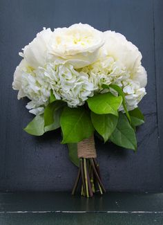 A classic white wedding bouquet of hydrangeas and peonies wrapped in twine. {One Eleven Images}