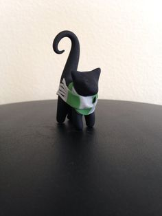 This cat is made to look like the Slytherin House from Harry Potter. He is black and has a silver and green scarf. Etsy