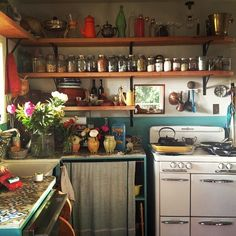 I like lots of things about this small cabin in Missouri (Google Search) including the open shelves, the curtains on the bottom shelving, and the old looking stove.