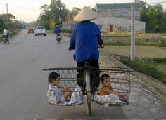 Sweet photo of a Bicycle used for 3, two little ones in side baskets for her bike. SOURCE: universenme on Twitter