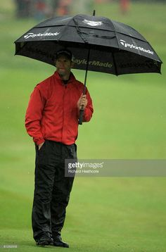 Bradley Dredge of Wales shelters under his umbrella before play is stopped for bad weather during the pro-am for The Celtic Manor Wales Open on the 2010 Golf Course at Celtic Manor on May 28, 2008 in Newport, Wales.