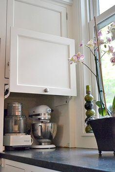 キッチンカウンターの端の壁に埋め込まれた平行にスイングアップする扉付きの中型調理器具収納スペース.jpg