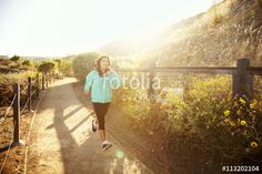 """Download the royalty-free photo """"Woman jogging down outdoor path"""" created by Cavan Images at the lowest price on Fotolia.com. Browse our cheap image bank online to find the perfect stock photo for your marketing projects!"""