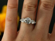 Ladies three stone engagement ring containing 1 round Forever Brilliant Moissanites and 2 pear shape NEo moissanites, styled in 14k white gold.  If you are looking for matching wedding band we will be more than happy to select or design one for you.  RING DESCRIPTION Style # KR-4733 Material - 14K , 18K White Gold/ 14K, 18K Yellow Gold/ 14K, 18K Rose Gold/ Platinum Moissanite cut - round and pear Center moissanite size - 7mm equal to diamond 1.25ct (Forever Brilliant) Side moissanite size…