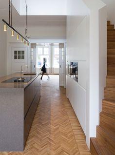minimal kitchen with herringbone parquet floor in Dutch townhouse//