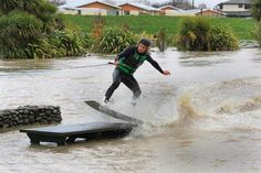 Michae Parkes slides across a picnic table while wakeboarding on the flooded Taylor River in central Blenheim