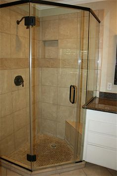 Master shower with shampoo shelf, corner seat and dark bronze fixtures. Storage/linen cabinet to the side of the shower make bathroom storage easy.