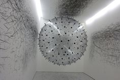 ADA – Analog Interactive Installation, is a kinetic sculpture by German-based artist Karina Smigla-Bobinski. The installation is made form an enormous helium-inflated sphere trapped inside a small room that's spiked with dozens of protruding charcoal pieces which scrape the edges of the gallery wall as participants push, toss, and otherwise manipulate it.